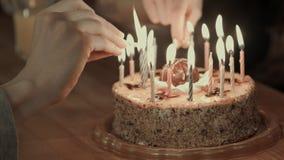 Dos personas que encienden los candels en una torta de cumpleaños Imagen de archivo libre de regalías