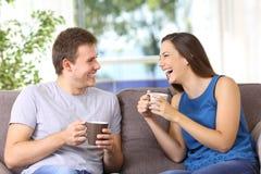 Dos personas que hablan y que se ríen a casa Imagen de archivo
