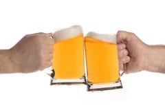 Dos personas que hacen una tostada con las tazas de cerveza Foto de archivo libre de regalías