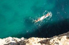 Dos personas que practica surf a bordo Imágenes de archivo libres de regalías