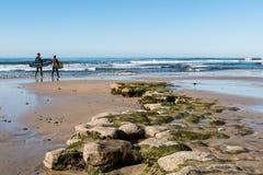 Dos personas que practica surf de sexo masculino caminan filón Alga-cubierto pasado durante la bajamar en la playa del ` s del Sw Fotografía de archivo libre de regalías