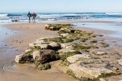 Dos personas que practica surf de sexo masculino caminan hacia el océano durante la bajamar en la playa del ` s del Swami Foto de archivo
