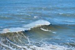 Dos personas que practica surf de sexo masculino cogen la onda grande en Nazare, equipo de la seguridad portugal Fotografía de archivo libre de regalías