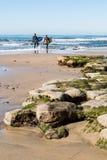 Dos personas que practica surf de sexo masculino que llevan las tablas hawaianas caminan en el océano en la playa del ` s del Swa Fotografía de archivo libre de regalías