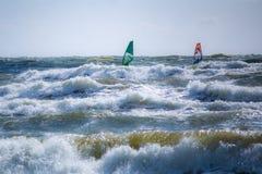 Dos personas que practica surf en el mar Báltico tempestuoso en Lituania imagenes de archivo