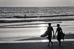 Dos personas que practica surf en la playa Imagenes de archivo