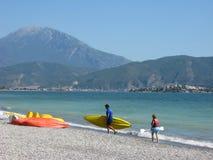 Dos personas que practica surf en la playa y la montaña enorme en fondo foto de archivo