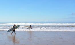 Dos personas que practica surf que llevan una tabla hawaiana en la playa cerca de Essaouira Foto de archivo