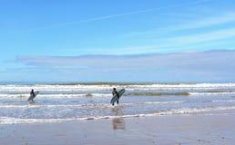 Dos personas que practica surf que llevan una tabla hawaiana en la playa cerca de Essaouira Imagenes de archivo