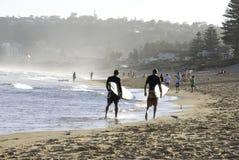 Dos personas que practica surf que caminan a lo largo de una playa Imágenes de archivo libres de regalías