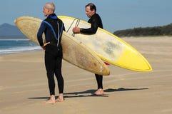 Dos personas que practica surf que miran las ondas Imagen de archivo libre de regalías