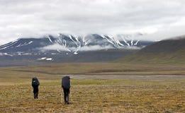 Dos personas que recorren en tundra en Svalbard Foto de archivo