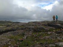 Dos personas que se colocan encima de una montaña Fotografía de archivo libre de regalías