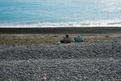 Dos personas que se relajan en un Pebble Beach por el mar de la turquesa Terraplén de la ciudad francesa famosa de Niza foto de archivo