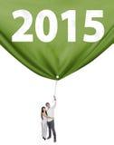 Dos personas que tiran de un Año Nuevo de la bandera Imagen de archivo libre de regalías