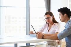 Dos personas que trabajan con la tableta digital en sala de reunión vacía Imagen de archivo libre de regalías