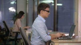 Dos personas que trabajan en el ordenador portátil en la oficina grande, soporte técnico, centro de servicio metrajes