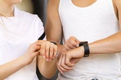 Dos personas que usan el reloj elegante del deporte en el entrenamiento Fotos de archivo libres de regalías