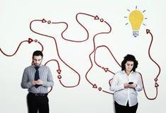 Dos personas que usan smartphones contra una pared blanca dibujada imagenes de archivo