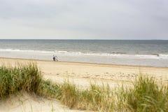 Dos personas que vagan a lo largo de la costa costa del Mar del Norte en el oeste de los Países Bajos imagen de archivo libre de regalías