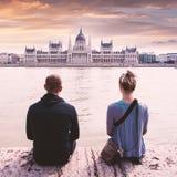 Dos personas se sientan en la costa y disfrutan de la opinión el parlamento en Budapest, Hungría fotos de archivo libres de regalías