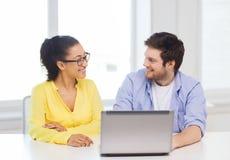 Dos personas sonrientes con el ordenador portátil en oficina Imágenes de archivo libres de regalías