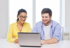 Dos personas sonrientes con el ordenador portátil en oficina Fotografía de archivo