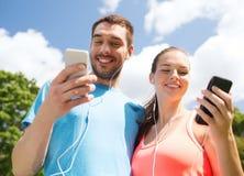 Dos personas sonrientes con smartphones al aire libre Imágenes de archivo libres de regalías