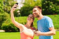 Dos personas sonrientes con smartphones al aire libre Foto de archivo