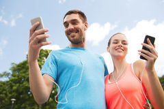 Dos personas sonrientes con smartphones al aire libre Foto de archivo libre de regalías