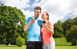 Dos personas sonrientes con smartphones al aire libre Imagen de archivo libre de regalías
