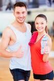 Dos personas sonrientes en el gimnasio Imagen de archivo libre de regalías