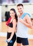 Dos personas sonrientes en el gimnasio Foto de archivo libre de regalías