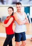 Dos personas sonrientes en el gimnasio Fotografía de archivo libre de regalías