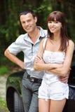 Dos personas sonrientes jovenes acercan al coche Fotografía de archivo