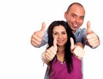Dos personas sonrientes jovenes con los pulgares-para arriba gesticulan aislado en pizca Imagen de archivo