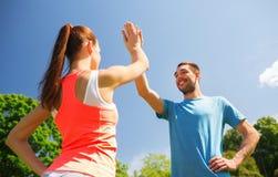 Dos personas sonrientes que hacen el alto cinco al aire libre Fotografía de archivo