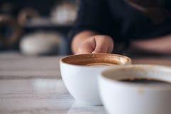 Dos personas tintinean las tazas del café con leche Imagenes de archivo
