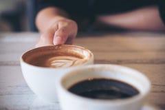 Dos personas tintinean las tazas del café con leche Fotos de archivo libres de regalías