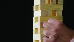 Dos personas toman vueltas que sacan barras de madera de la torre el jugar en Jenga almacen de metraje de vídeo