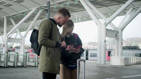 Dos personas urbanas fuera del aeropuerto con equipaje almacen de video