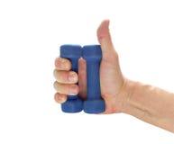 Dos pesas de gimnasia azules encendido sirven la palma, pulgares para arriba Foto de archivo
