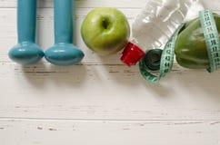 Dos pesas de gimnasia, botella de agua, manzana verde, centímetro en blanco Fotografía de archivo libre de regalías