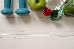 Dos pesas de gimnasia, botella de agua, manzana verde, centímetro en blanco Fotos de archivo libres de regalías