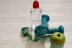 Dos pesas de gimnasia, botella de agua, manzana verde, centímetro en blanco Foto de archivo