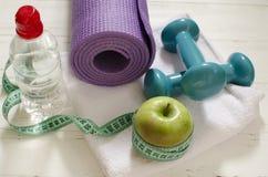 Dos pesas de gimnasia, botella de agua, manzana verde, centímetro en blanco Imagen de archivo libre de regalías