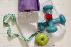 Dos pesas de gimnasia, botella de agua, manzana verde, centímetro en blanco Fotografía de archivo