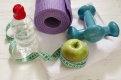 Dos pesas de gimnasia, botella de agua, manzana verde, centímetro en blanco Imagenes de archivo