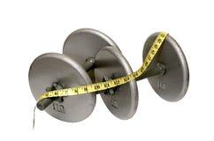 Dos pesas de gimnasia con la cinta de medición aislada Imágenes de archivo libres de regalías