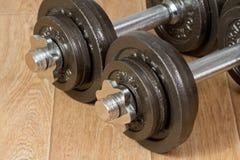 Dos pesas de gimnasia que se colocan en piso de madera Foto de archivo